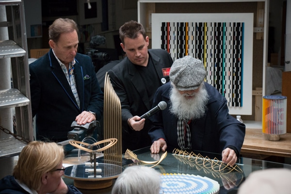 Yaacov Agam demonstrates his Beating Heart sculpture to Park West VIP guests at a studio visit celebrating his 86th birthday. Park West's Jason Betteridge and founder and CEO Albert Scaglione look on.