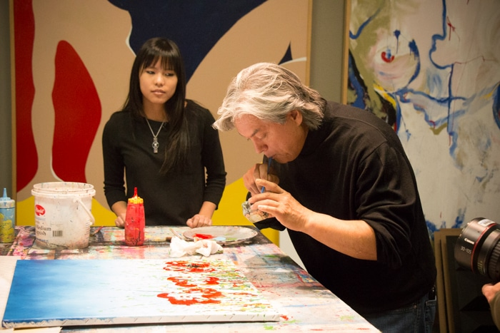Dominic Pangborn demonstrates for the TV crew and a student a primitive airbrush technique using a straw.
