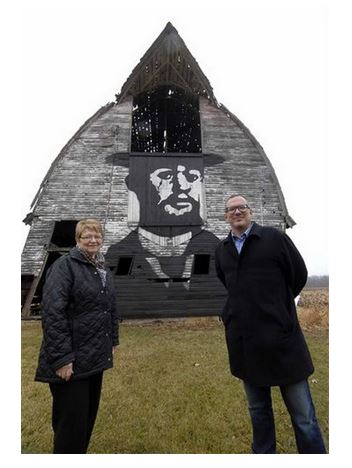 Joan Peterson, left, of Clive, and her son, Curt Peterson of Des Moines, stand in front of their barn, upon which they painted a portrait of Henri de Toulouse-Lautrec. Image captured from Miami Herald. Original photo by Hans Madsen.
