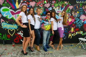 Romero Britto with five Miss Universe contestants in front of their mural. Photo credit: Haute Living
