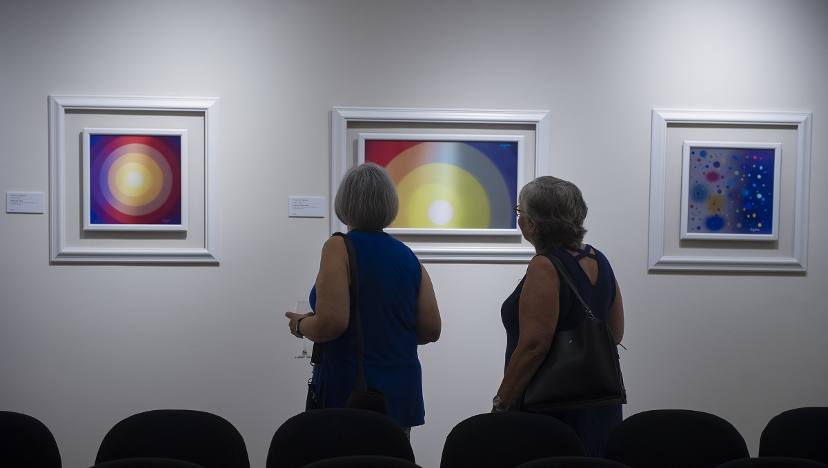 Guests observe artwork by Yaacov Agam at Park West Gallery.