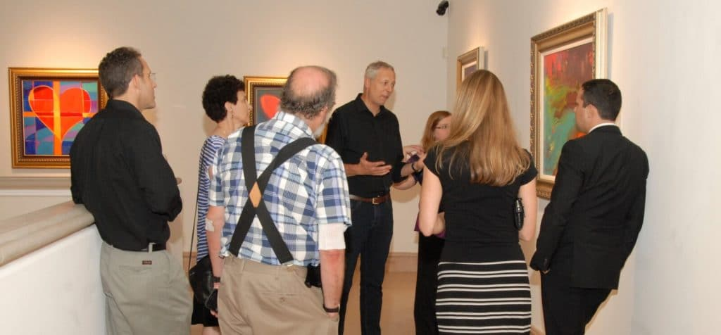 "Simon Bull discussing his artwork during his exhibition ""Language of Color."""