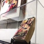 One of Pino's famous book covers displayed next to the artist's original painting for the cover.