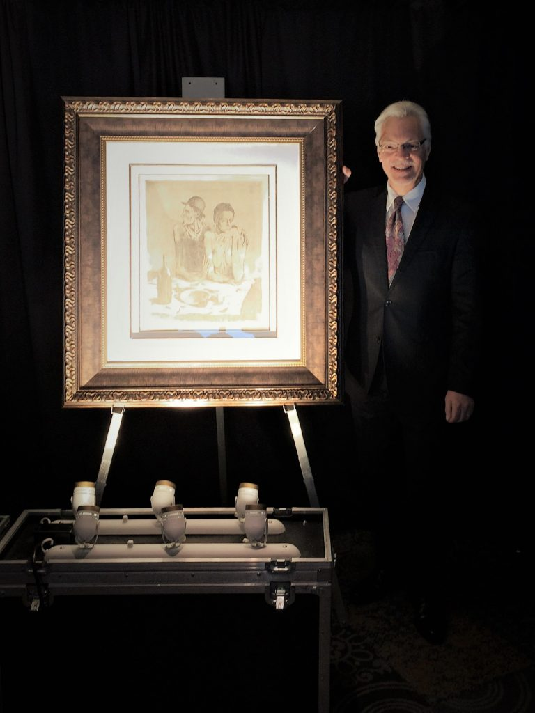 Art Gallery Director stands with a large framed picasso etching