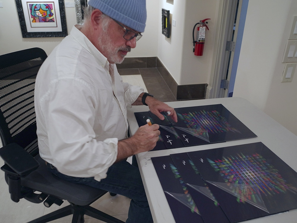 "Ron Agam signs editions of his ""New York"" 3-DK art."