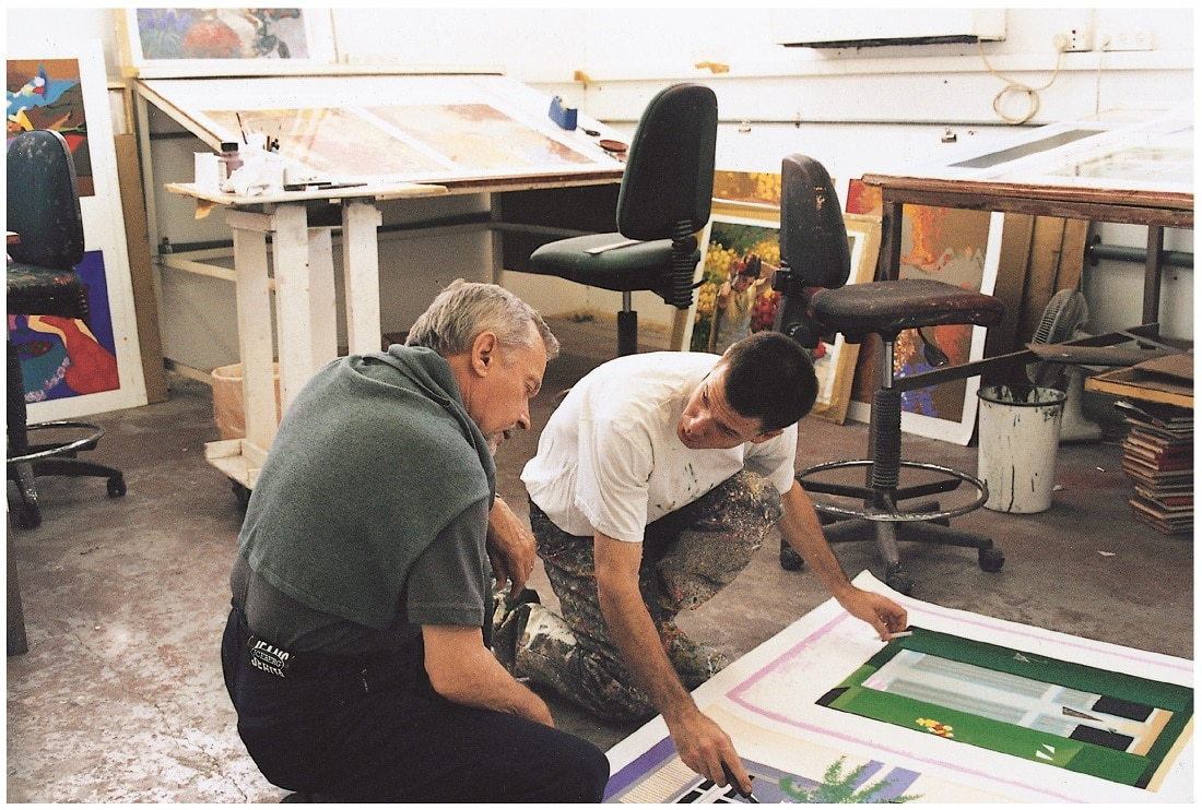 Artist Igor Medvedev checking the colors on an in-progress serigraph in his studio.
