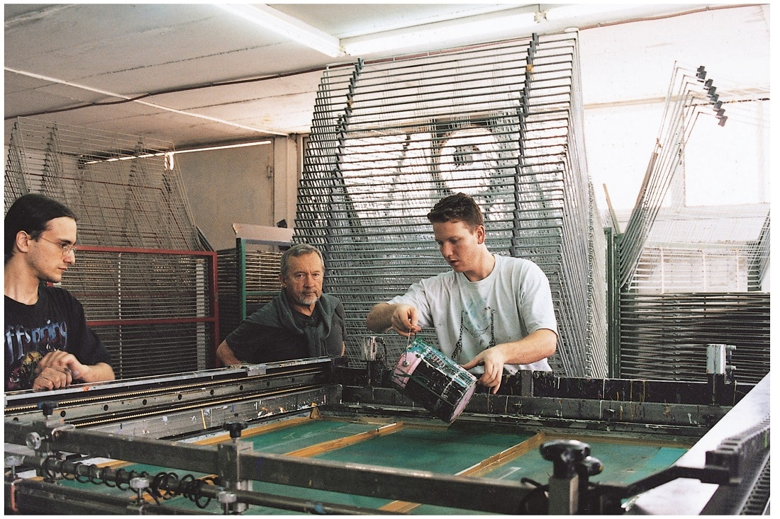 Medvedev watches as artisans spread color over the silkscreen during the serigraphy process