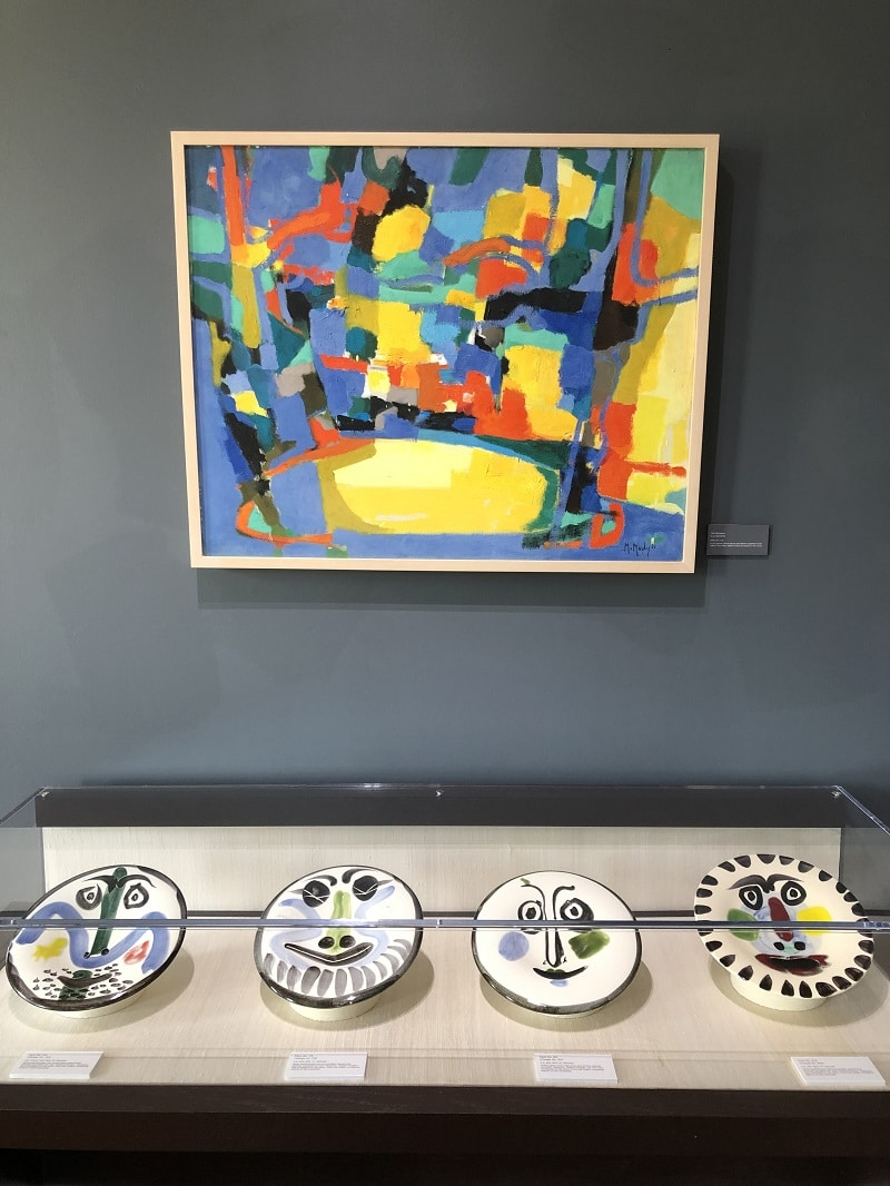 """""""The Meadow (La Clairiére; 1960), Marcel Mouly, hanging above a selection of Picasso's ceramic works"""