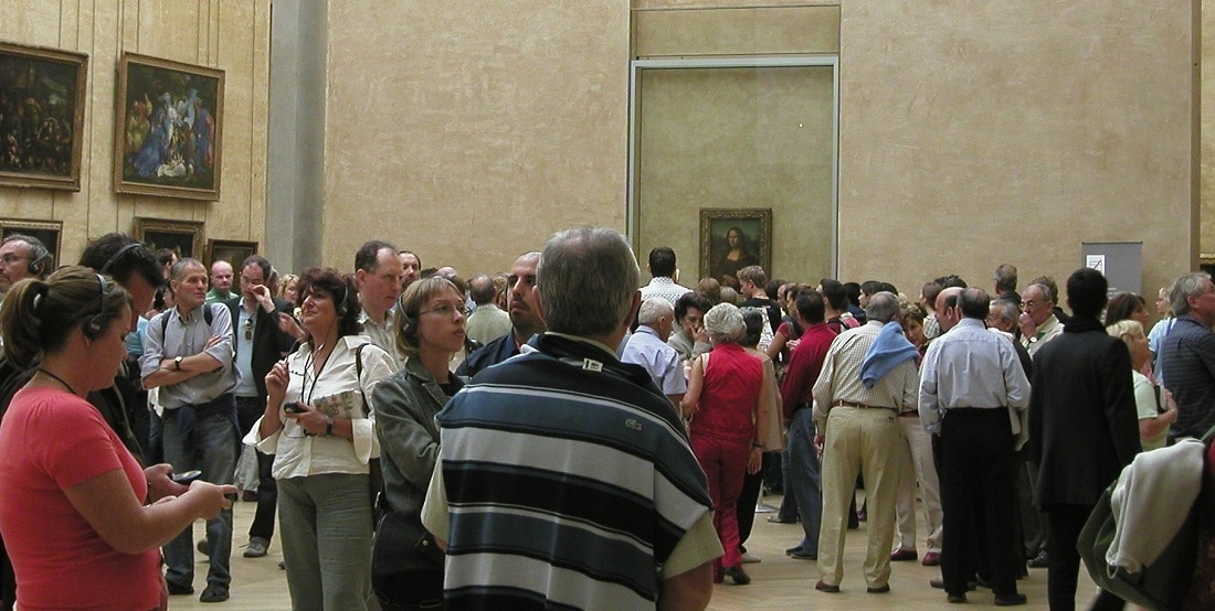 "Crowds navigate the ""Mona Lisa"" gallery at the Louvre"