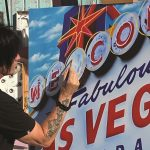 Michael Godard paints one of his olives (and a tribute to his hometown) in Las Vegas' Neon Museum.