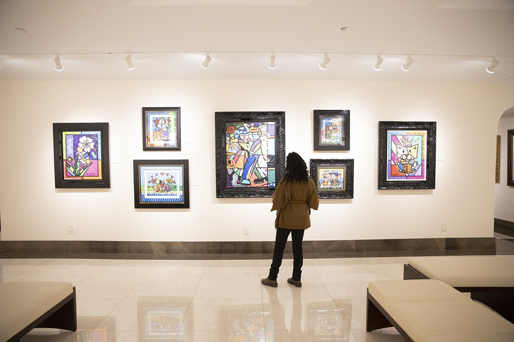 A visitor browses a wall of works by artist Romero Britto in Park West Museum's downstairs gallery space.
