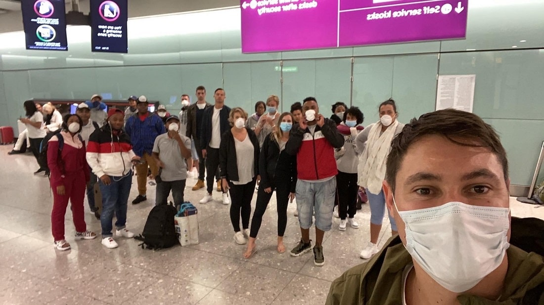Auctioneer Jared Hamer poses with stranded cruise ship workers at London's Gatwick airport.