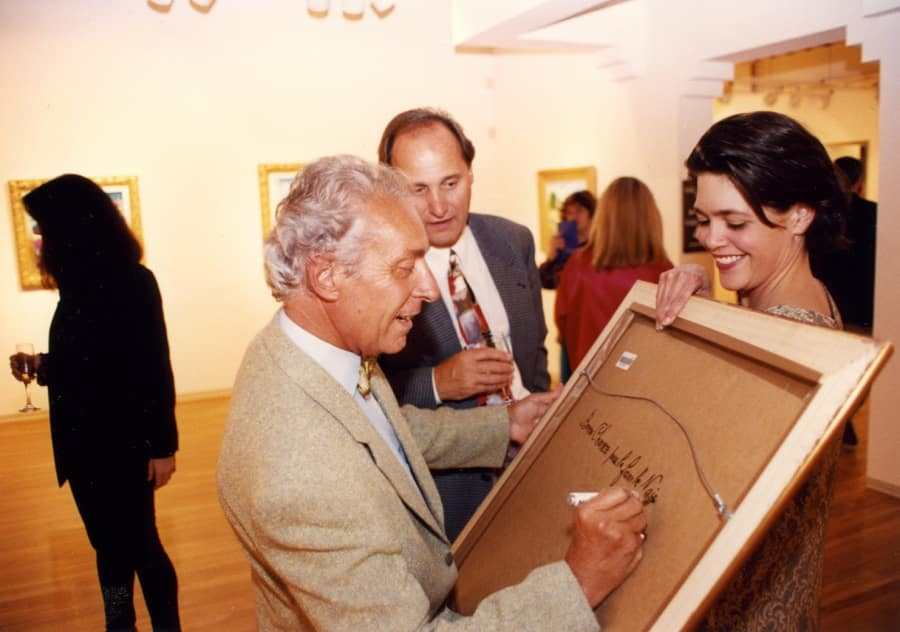 Picot signing a painting for an excited fan at the opening of a 2010 Park West exhibition.
